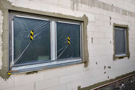 Windows of a house under construction covered with protective plastic film. Stock fotó