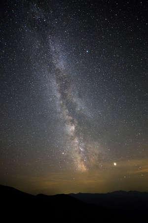 Paesaggio notturno di montagne con cielo coperto di stelle.