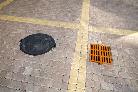 Stara zardzewiała metalowa rynna na wodę deszczową na chodniku wyłożonym kamieniem.