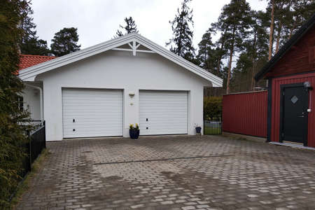 White new garage for two cars and wooden barn on private house yard.