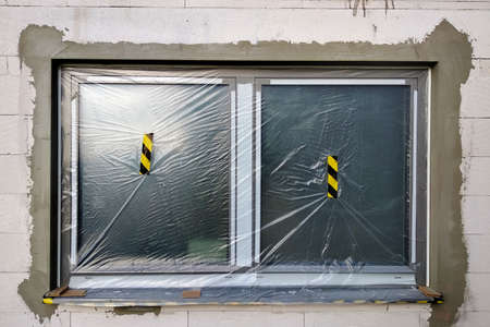 Window of a house under construction covered with protective plastic film. Stock fotó