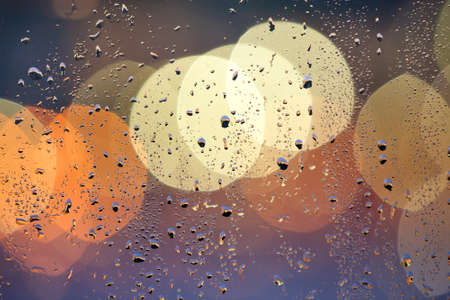 Abstract colorful bokeh background with yellow circles and water drops on glass surface in front. Blurred city lights. Stock Photo