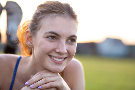 Close up portrait of cheerful smiling young girl with freckles on her face outdoors in sunny summer day. Human expressions and emotions concept.