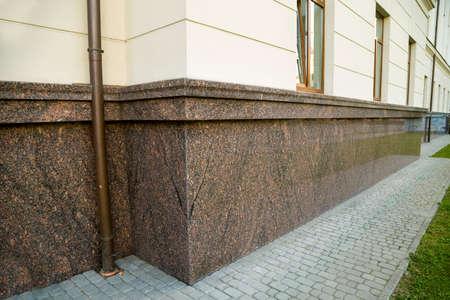 Nahaufnahme eines Teils einer Gebäudefassade mit der Oberfläche der Granitwand. Natursteinmaterialien. Standard-Bild