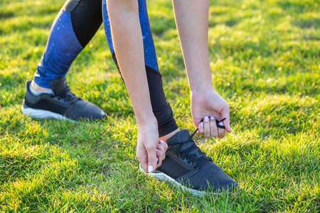 Close-up of female hands tying shoelace on running shoes before practice. Runner getting ready for training. Sport active lifestyle concept.