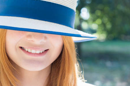 Portrait of gorgeous smiling teenage girl in yellow hat and with red hair outdoors on sunny summer day.