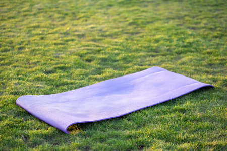 Blue mat for yoga or fitness on green grass lawn outdoors.