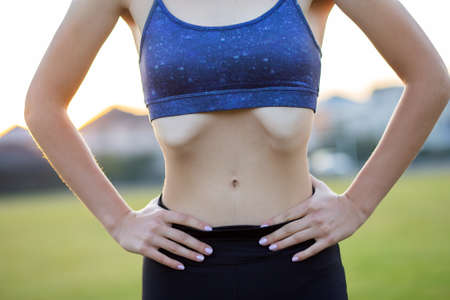 Closeup of a girl slim body in sports clothes. Flat stomach as result of physical training. Stok Fotoğraf