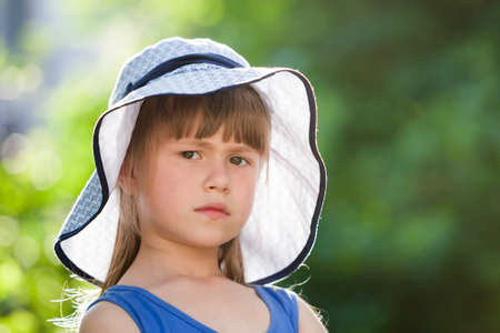 Close-up portrait of serious little girl in a big hat. Child having fun time outdoors in summer.