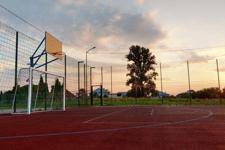 Outdoors mini football and basketball court with ball gate and basket surrounded with high protective fence. Stok Fotoğraf