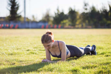 Young sportive woman in sports clothes training in field at sunrise. Girl standing in plank position on grass in a city park.