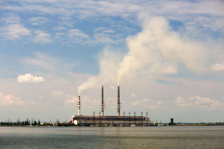 Thermal power station tall pipes with thick smoke reflected in lke water surface. Pollution of environment concept.