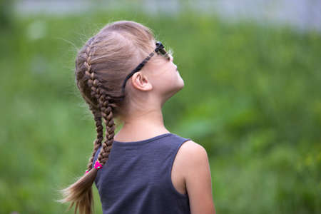 Portrait of pretty child girl with braids in hair outdoors in summer. Stok Fotoğraf