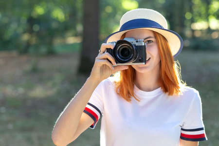 Pretty teenage girl with red hair taking picture with photo camera in summer park. Stok Fotoğraf