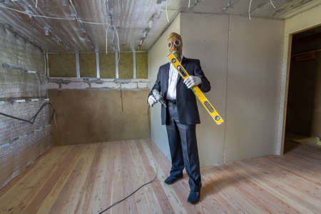Strange man in businessman suit and gas protection mask inside a room under renovation works holding electric screwdriver and a level tools.