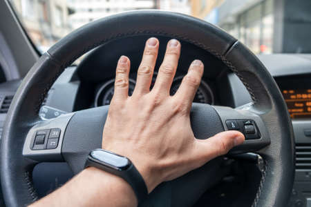 Drivers hand on a steering wheel of a car.