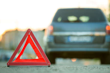 Red emergency triangle stop sign and broken car on a city street. Stock fotó