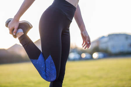 Closeup of young sportive woman doing exercise before running in morning field outdoors. Imagens