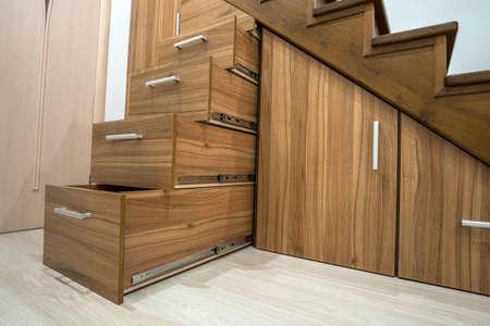 Modernes Architekturinterieur mit Luxusflur mit glänzender Holztreppe im mehrstöckigen Haus. Maßgefertigte ausziehbare Schränke auf Gleitern in Schlitzen unter Treppen. Nutzung des Lagerraums.