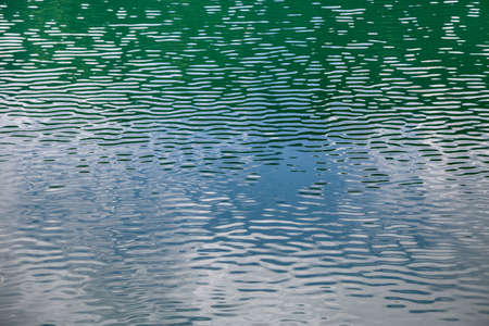 Close up detail of water surface with ripples on it.