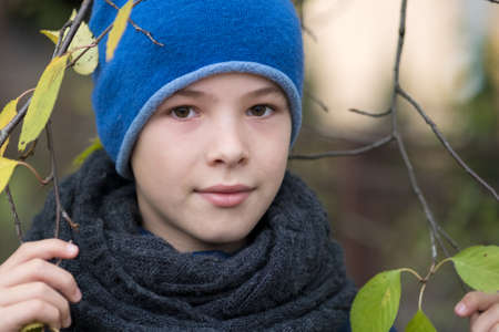 Pretty child boy wearing warm winter clothes holding tree branch with green leaves in cold weather outdoors. Stock Photo