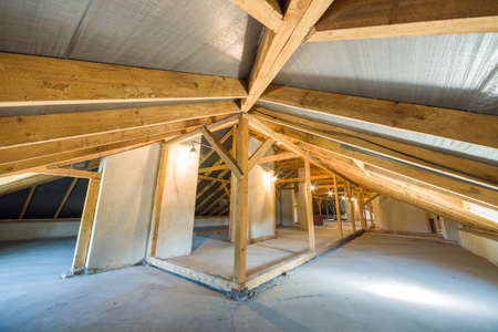 Attic of a building with wooden beams of a roof structure. Фото со стока