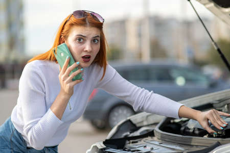 Young woman standing near broken car with popped hood talking on her mobile phone while waiting for help.