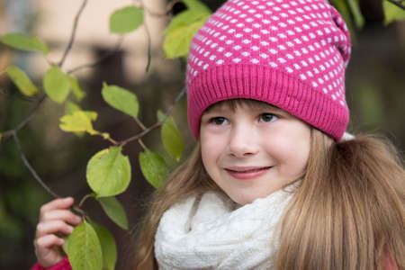 Pretty child girl wearing warm winter clothes holding tree branch with green leaves in cold weather outdoors. Stockfoto