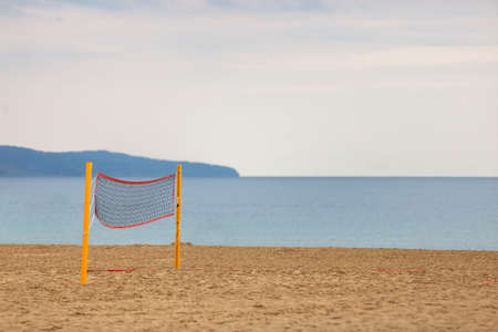 Empty volleyball net on a sandy beach on the sea shore in summer.