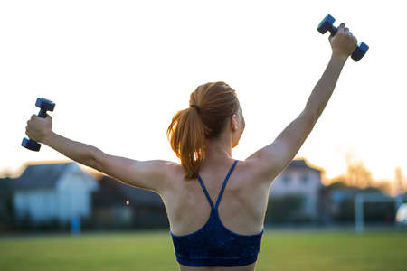 Portrait of athletic teenage girl in fitness wear exercising with blue dumbbells outdoors in park. Fit young woman working out outside.