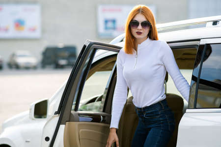 Yong pretty woman standing near a big all terrain car outdoors. Driver girl in casual clothes outside her vehicle.