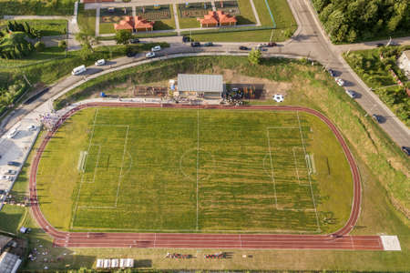 Aerial view of a football field on a stadium covered with green grass in rural town area. Archivio Fotografico - 134714292