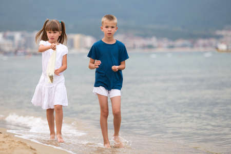 Two children boy and girl walking barefoot on sea shore water in summer.