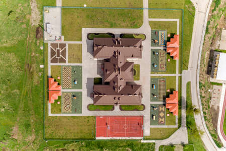 Top aerial view of new prescool building and yard with alcoves and green lawns. Archivio Fotografico - 134714973