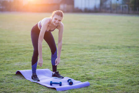 Slim blonde girl plays sports and performs yoga poses in summer grass covered stadium on a sunset background. Woman doing exercises on the yoga mat.