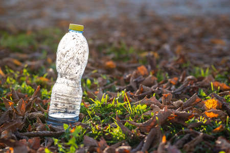 Used plastic bottle thrown away on grass covered ground outdoors. Pollution of nature concept. Stock Photo - 134715597