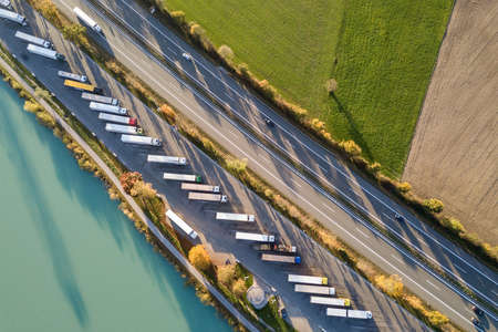 Top down aerial view of highway interstate road with fast moving traffic and parking lot with parked lorry trucks. Stockfoto
