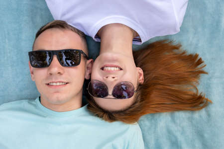 Young teenage couple in sunglasses laying together on blue cloth enjoying love relations. Standard-Bild - 134716200