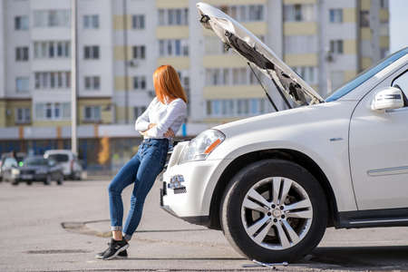 Young stressed woman driver standing near broken car with open hood.