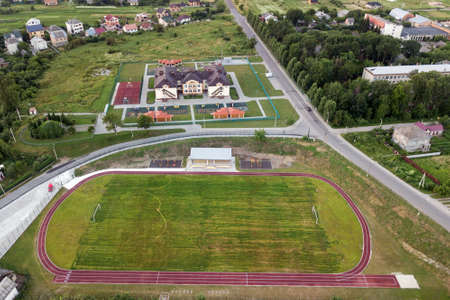 Aerial view of a football field on a stadium covered with green grass in rural town area. Archivio Fotografico - 134716641