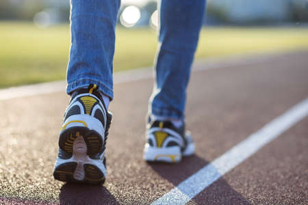 Close up of woman feet in sport sneakers and blue jeans on running lane on outdoor sports court.