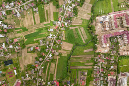 Top down aerial view of town or village with rows of buildings and curvy streets between green fields in summer. Countryside landscape from above.