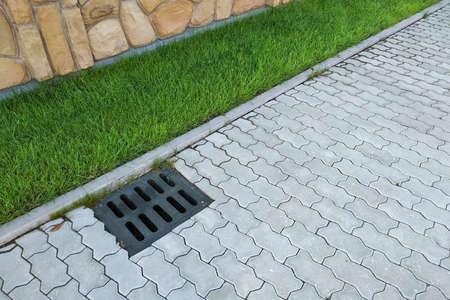 Plastic drain gutter, green grass lawn and stone pavement sidewalk.