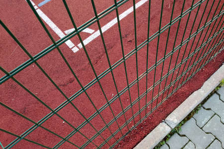 Close-up of white marking lines of outdoor basketball court fenced with protective metal fence. Archivio Fotografico - 134722481