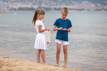 Two children boy and girl walking barefoot on sea shore water in summer. Stockfoto - 134722852