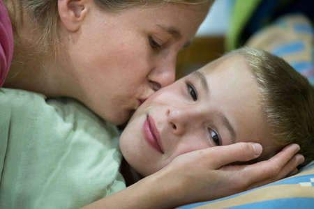Happy mother gives her son a kiss before sleep and wish good night and beautiful dreams. Фото со стока - 134723036