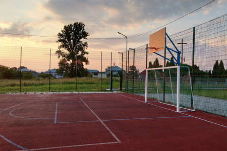 Outdoors mini football and basketball court with ball gate and basket surrounded with high protective fence. Archivio Fotografico - 134723043