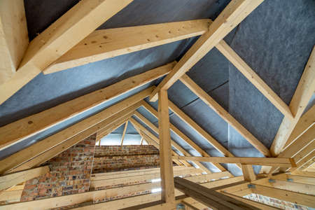 Attic space of a building under construction with wooden beams of a roof structure and brick walls. Real estate development concept.