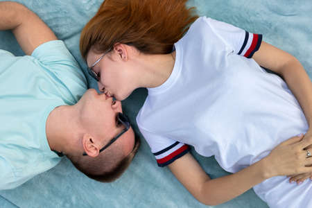 Young teenage couple in sunglasses laying together on blue cloth enjoying love relations and kissing. Standard-Bild - 134723156