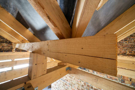 Attic of a building under construction with wooden beams of a roof structure and brick walls.